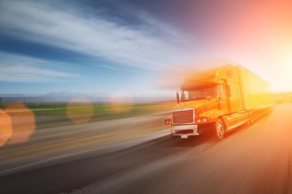 Truck speeding on freeway at sunset. Blurred motion.