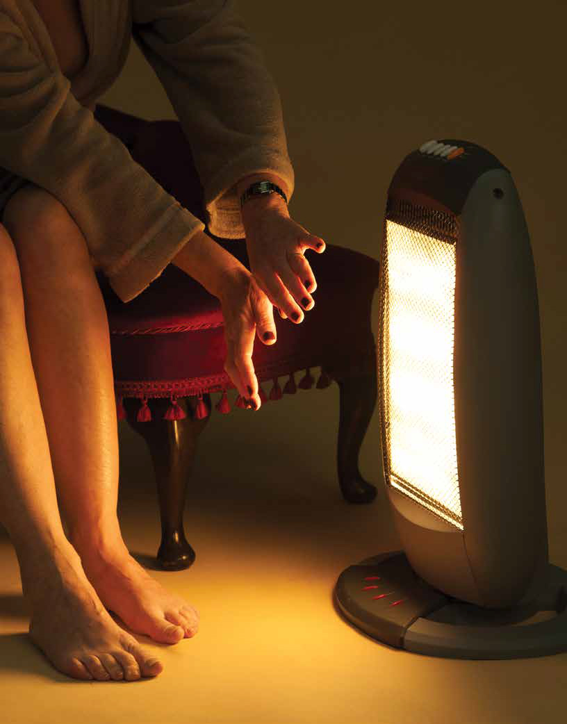 Woman keeping warm by an electric fire
