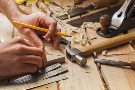 carpenter working,hammer,meter and screw-driver on construction background
