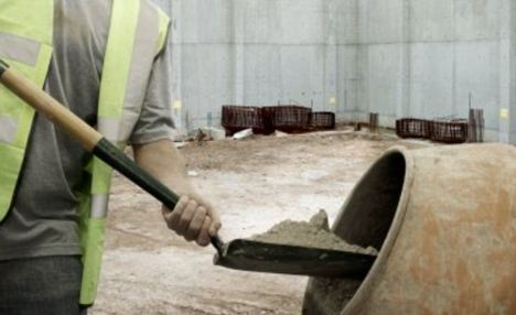 Builder shovelling cement into mixer on building site