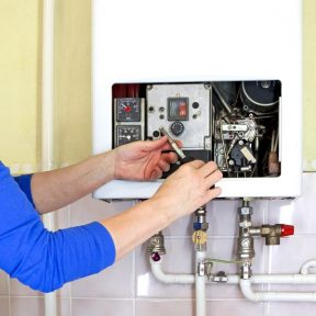 repairman fixing a gas heating with screwdriver
