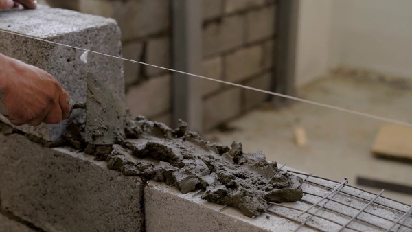 videoblocks-worker-is-applying-cement-mortar-on-a-wall-for-lying-building-blocks-distributing-evenly-using-spatula_heh78v2pg_thumbnail-full01