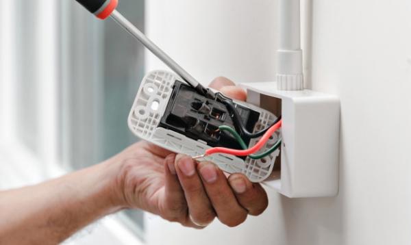 electricista-utilizando-destornillador-conectar-cable-alimentacion-toma-corriente_47469-242