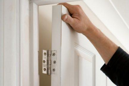 a-builder-fixing-a-door-to-a-hinge-87297970-57cd965a5f9b5829f4f1f56a