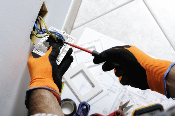 Electrician working safely on switches and sockets of a residential electrical system