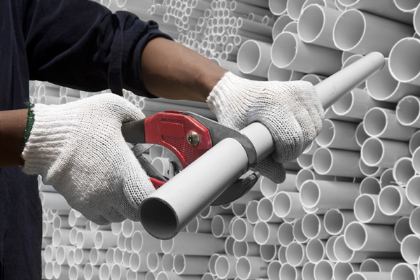 18942662 - worker cutting pvc pipe in construction site