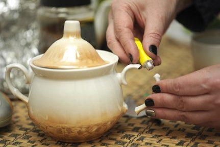 Manicured female hands gluing a broken sugar bowl, macro shot
