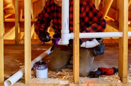 Applying plumber pipe drain and vent plumbing system at renovation new home construction