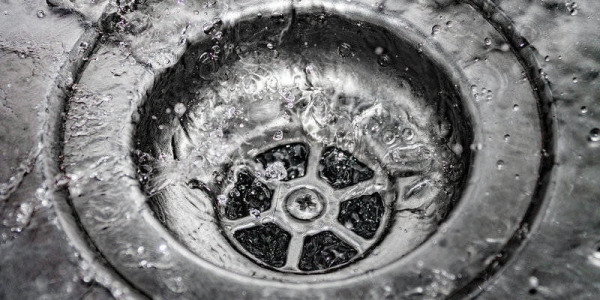 Water drains into the sink, sink and running water for the background, takes care of the water