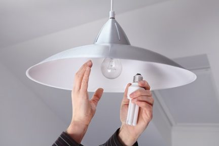 Person Changing Bulbs to Save Energy