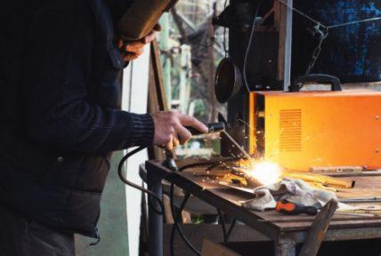Man welding old shovel, close up