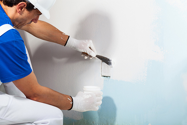 Close-up Of Professional Workman Applying Plaster on the Wall With Putty Knife