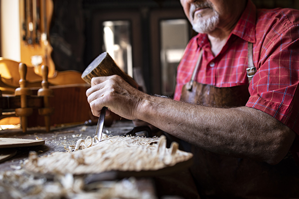 An old fashioned experienced senior carpenter holding knife and hammer carving wooden board in his woodworking workshop.