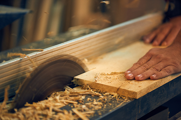 Professional carpenter using circular saw in his carpentry workshop. Focus on a saw