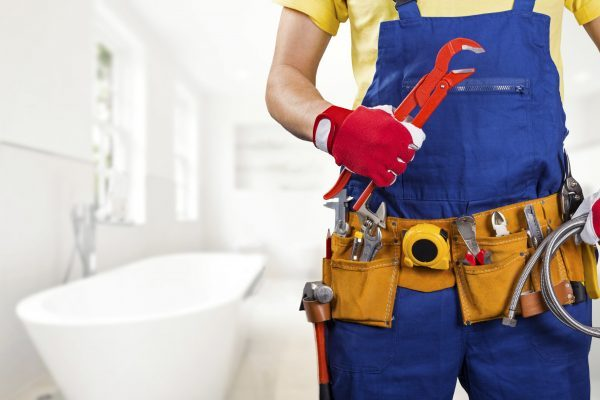 plumber with tool belt and wrench in hand standing in bathroom